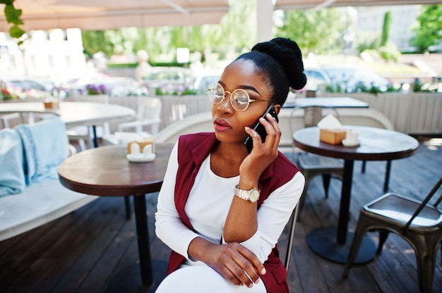 African american girl wear in glasses with mobile phone sitting at outdoor caffe.