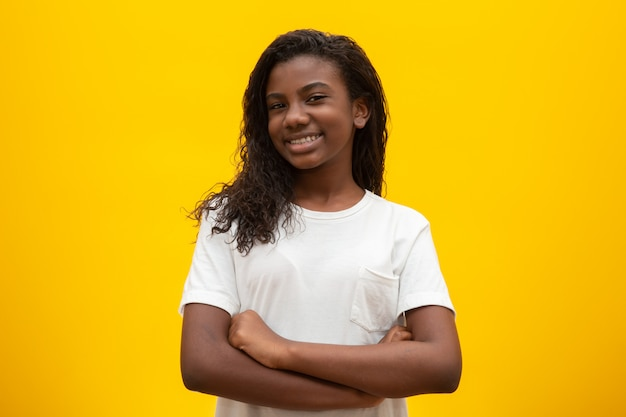 African american girl with curly hair on yellow . smiling black kid with a black power hair. black girl with a black power hair. african descent.