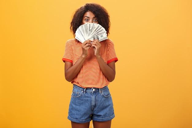 돈 무리 뒤에 얼굴을 숨기고 곱슬 헤어 스타일으로 아프리카 계 미국인 여자