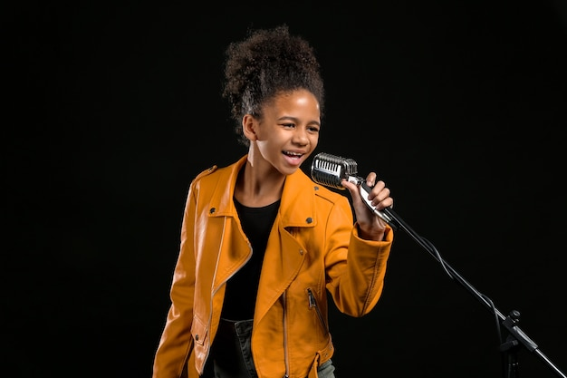 African-american girl with microphone singing, isolated on black