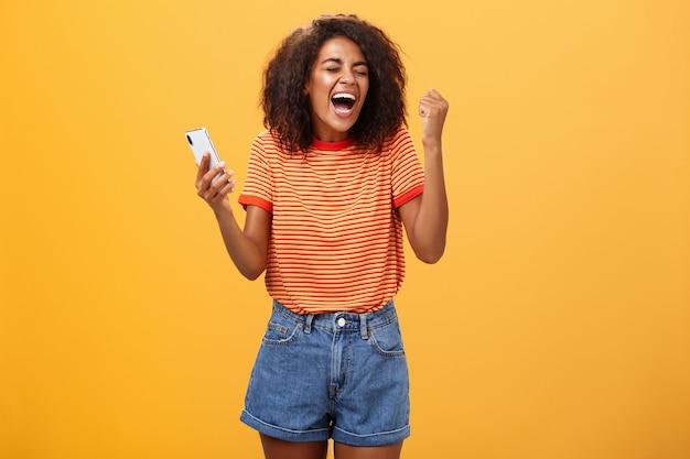 オレンジ色の壁にスマートフォンを持って拳を握りしめ幸せから叫んでアフリカ系アメリカ人の女の子