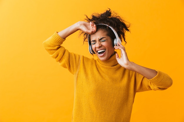 African american glad woman in casual clothing listening to music via white headphones, isolated
