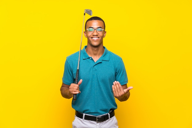 African american golfer player man inviting to come with hand. happy that you came