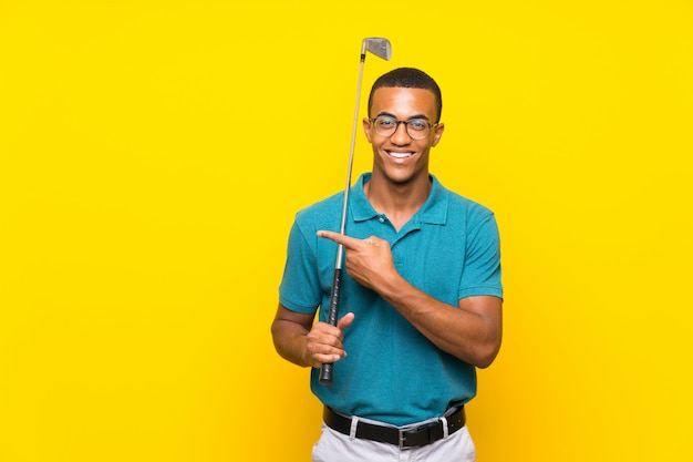 African american golfer player man pointing to the side to present a product