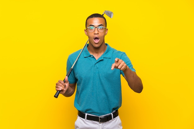 African american golfer player man surprised and pointing front
