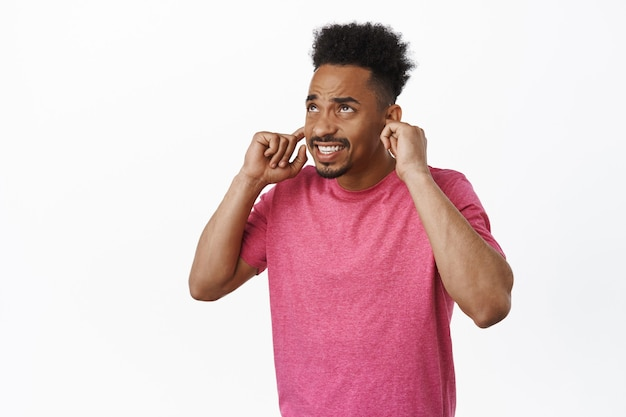 African american guy bothered by loud neighbours. young man shut ears with fingers, clench teeth and furrow eyebrows displeased, disturbed by annoying sound music on white