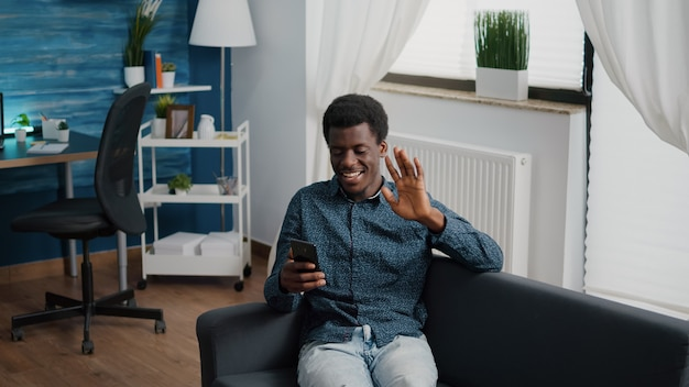 African american guy greeting colleagues or family while talking on online video conference call. working from home remote worker in distance communication chat, learning and connecting