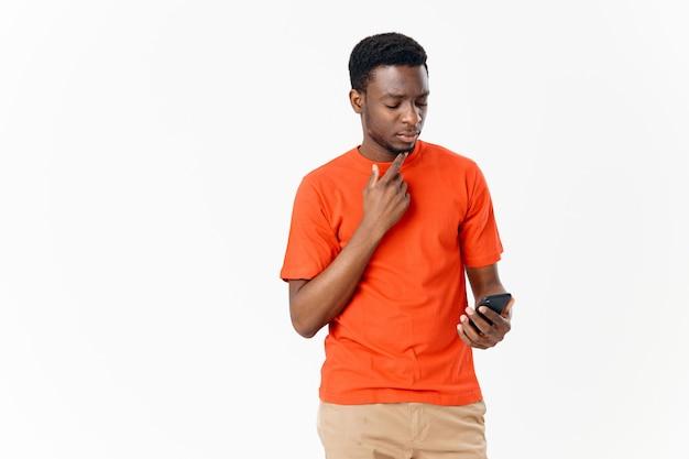 明るい背景に携帯電話とオレンジ色のtシャツを着たアフリカ系アメリカ人の男