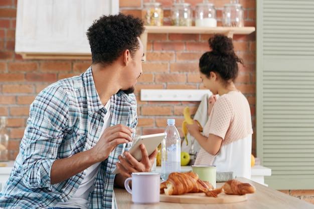 アフリカ系アメリカ人の男は妻またはガールフレンドを見て、バナナを与えるように彼女に頼み、台所のテーブルに座って、現代のタブレットコンピューターを使用しています