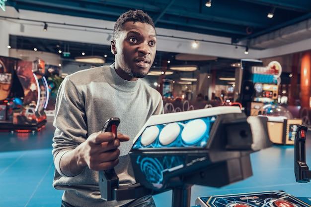 African american guy piloting spacecraft in arcade.