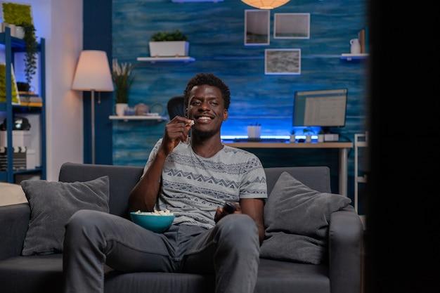 Афро-американский парень отдыхает на диване, смотрит комедию по телевидению