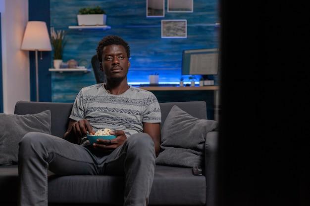 Афро-американский парень сидит на диване в гостиной с миской попкорна