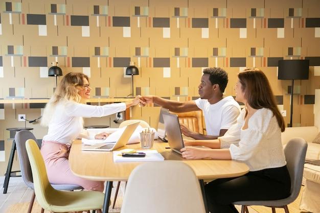 笑顔と金髪の女性のパートナーに挨拶アフリカ系アメリカ人の男