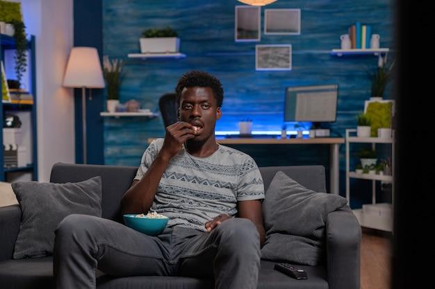 Афро-американский парень смотрит развлекательный фильм по телевизору, отдыхая на диване