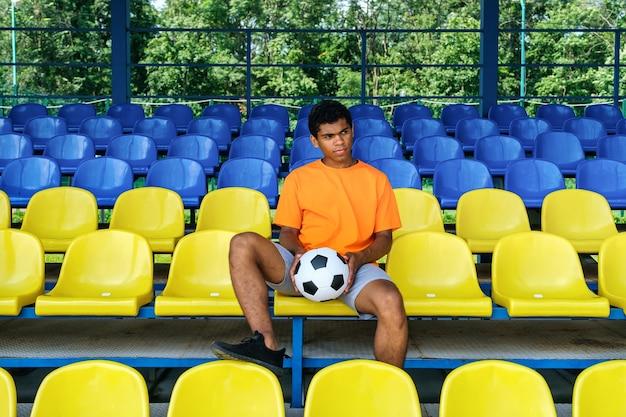 Афро-американский парень с футбольным мячом сидит на пустой футбольной трибуне