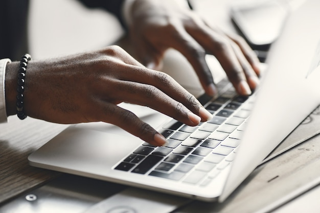 African american hands typing on a laptop.