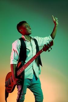 Musicista jazz afroamericano bello che tiene il basso elettrico e accoglie il pubblico