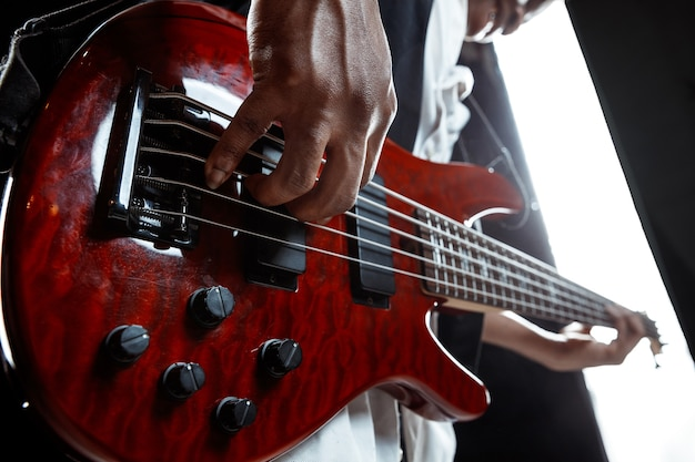 African american handsome jazz musician playing bass guitar in the studio on a black background. music concept. young joyful attractive guy improvising. close-up retro portrait.