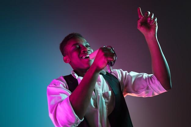 ネオンの背景でスタジオのマイクに向かって歌っているアフリカ系アメリカ人のハンサムなジャズミュージシャン。音楽のコンセプト。若いうれしそうな魅力的な男即興。クローズアップのレトロな肖像画。