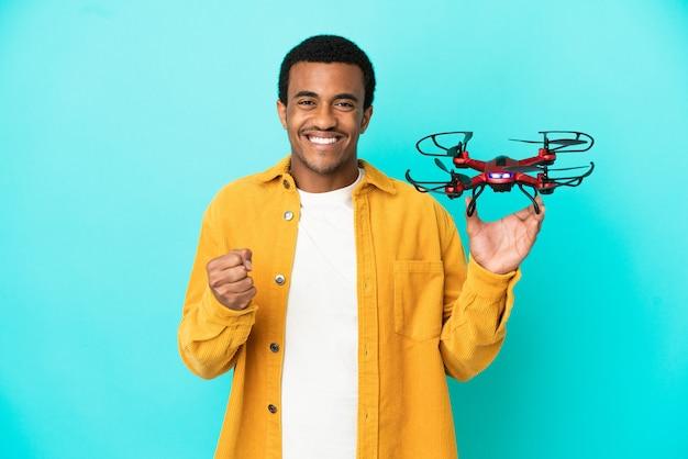 우승자 위치에서 승리를 축하하는 고립 된 파란색 배경 위에 무인 항공기를 들고 아프리카 계 미국인 잘생긴 남자