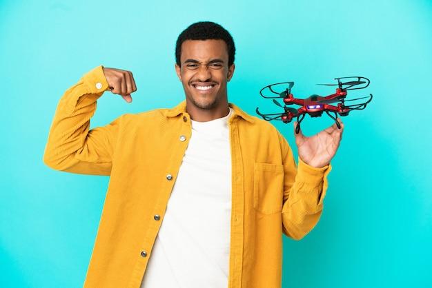 Афро-американский красавец, держащий дрон на синем фоне, делает сильный жест