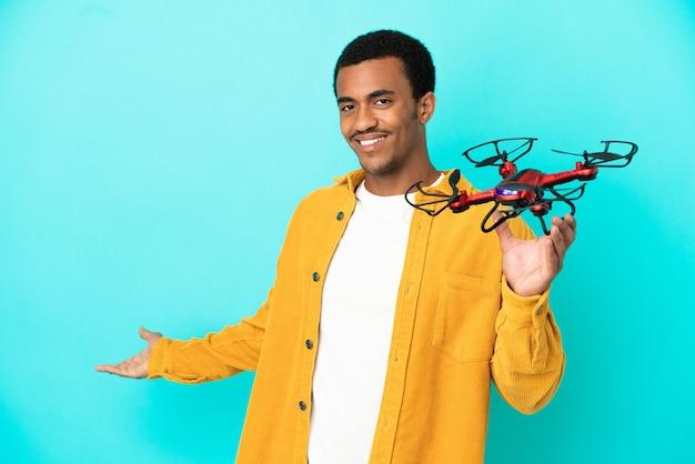 Афро-американский красавец держит дрон на синем фоне, протягивая руки в сторону, приглашая приехать