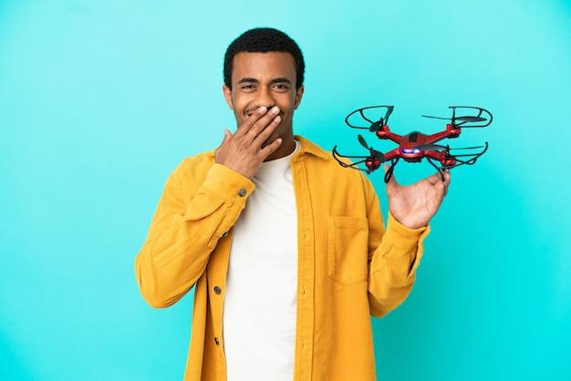 Афро-американский красавец, держащий дрон на синем фоне, счастливый и улыбающийся, прикрывая рот рукой