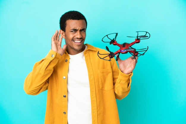 Афро-американский красавец, держащий дрон на синем фоне, слушает что-то, положив руку на ухо