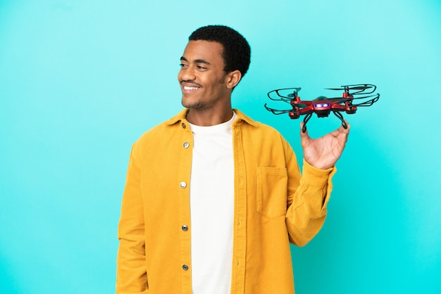 Афро-американский красавец, держащий дрон на синем фоне, глядя в сторону и улыбаясь