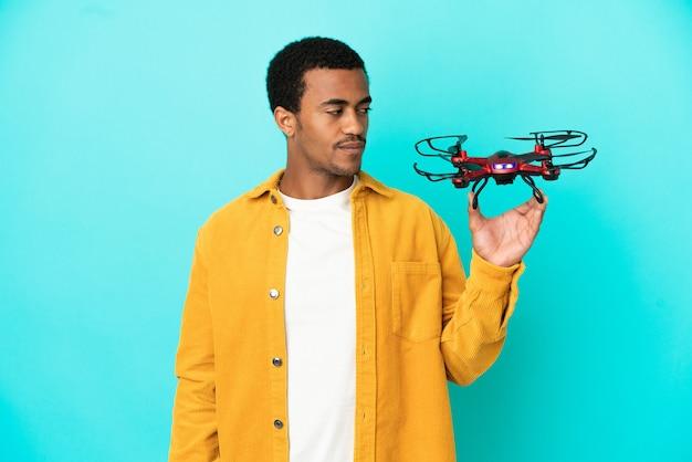Афро-американский красавец, держащий дрон на синем фоне, глядя в сторону