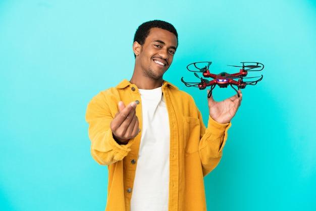 Афро-американский красавец, держащий дрон на синем фоне, делая денежный жест