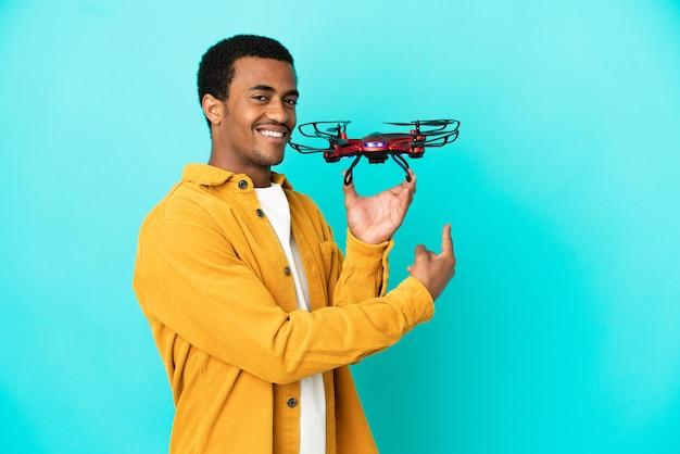 Афро-американский красавец, держащий дрон на синем фоне, указывая назад