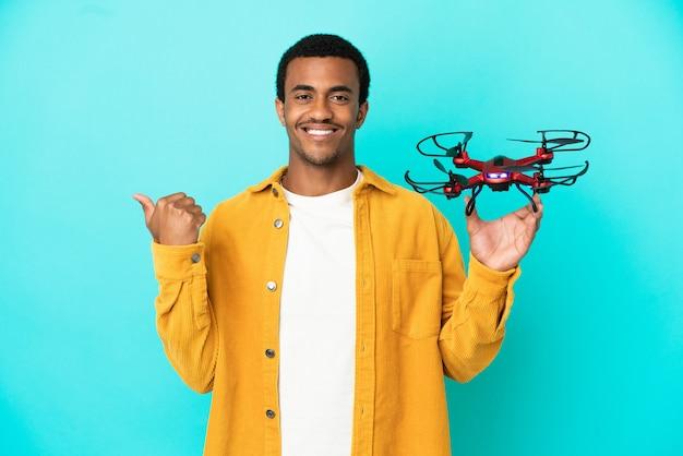 Афро-американский красавец держит дрон на синем фоне, указывая в сторону, чтобы представить продукт