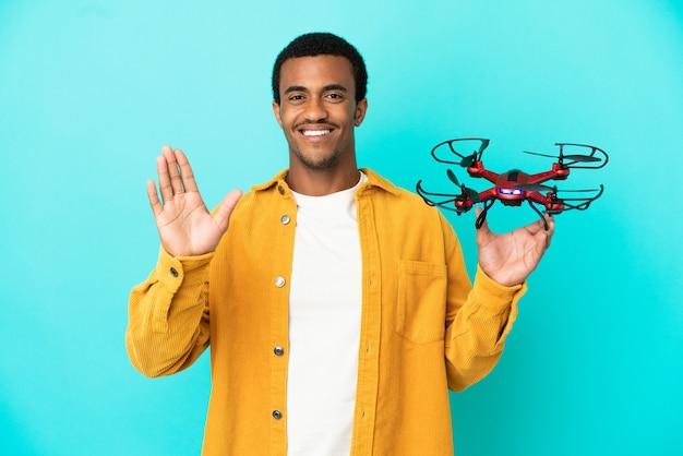 Афро-американский красавец, держащий дрон на синем фоне, салютует рукой с счастливым выражением лица