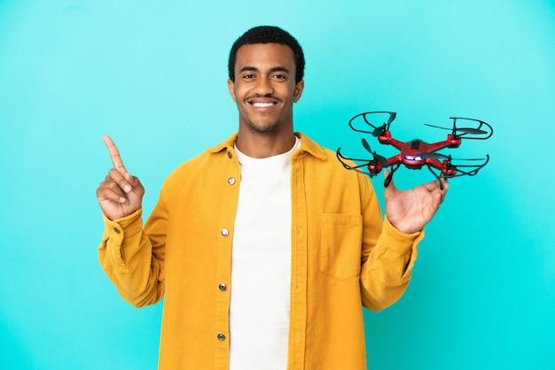 Афро-американский красавец, держащий дрон на синем фоне, показывает и поднимает палец в знак лучших