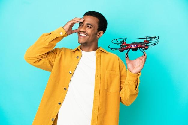 Афро-американский красавец, держащий дрон на синем фоне, много улыбаясь