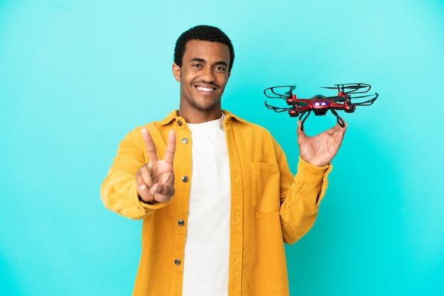 Афро-американский красавец, держащий дрон на синем фоне, улыбается и показывает знак победы