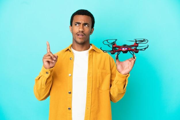 Афро-американский красавец держит дрон на синем фоне, думая об идее, указывая пальцем вверх