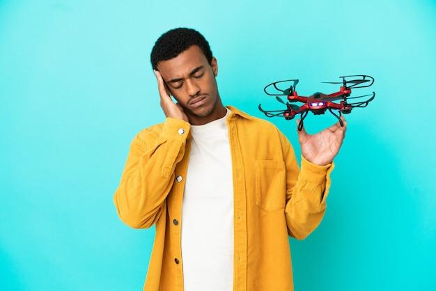 Афро-американский красавец, держащий дрон на синем фоне с головной болью