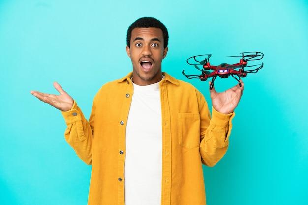 Афро-американский красавец держит дрон на синем фоне с шокированным выражением лица