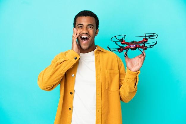 Афро-американский красавец держит дрон на синем фоне с удивлением и шокированным выражением лица