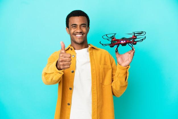 Афро-американский красавец держит дрон на синем фоне с большими пальцами руки вверх, потому что произошло что-то хорошее