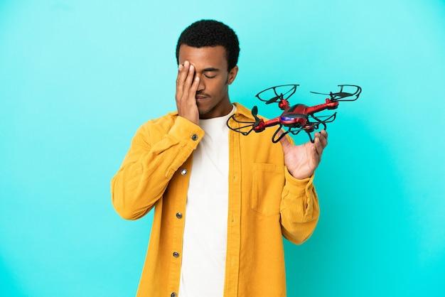 Афро-американский красавец, держащий дрон на синем фоне с усталым и больным выражением лица
