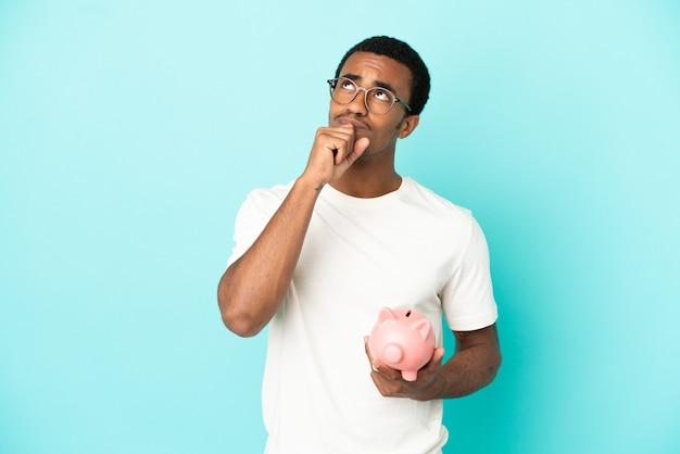 고립된 파란색 배경 위에 돼지 저금통을 들고 올려다보는 아프리카계 미국인 잘생긴 남자