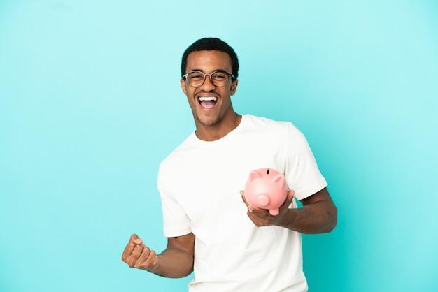 승리를 축하하는 고립 된 파란색 배경 위에 돼지 저금통을 들고 아프리카 계 미국인 잘 생긴 남자
