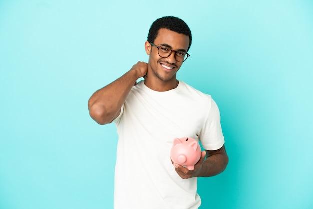 Афро-американский красавец, держащий копилку на синем фоне, смеясь