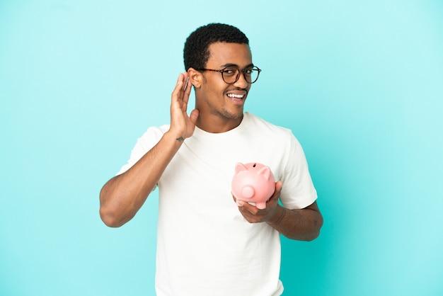 Афро-американский красавец держит копилку на синем фоне, слушая что-то, положив руку на ухо