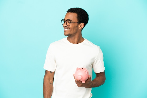 Афро-американский красавец, держащий копилку на синем фоне, глядя в сторону и улыбаясь