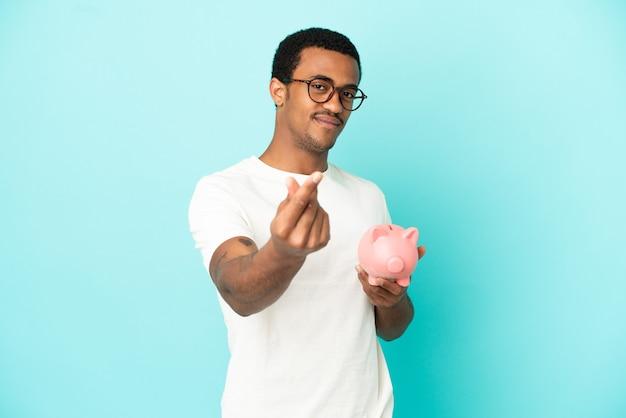 돈 제스처를 만드는 고립 된 파란색 배경 위에 돼지 저금통을 들고 아프리카 계 미국인 잘생긴 남자