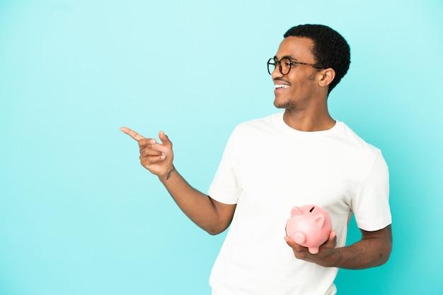 Афро-американский красавец держит копилку на синем фоне, указывая пальцем в сторону и представляет продукт